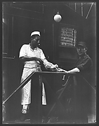 [Short Order Cook and Worker Playing Tug-of-War with Raw Meat Outside Lunchroom Doorway on Second Avenue, New York City]