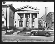 "[Greek Revival House on Street with ""Chicken Dinner"" and ""Garage for Rent"" Signs, Syracuse, New York]"
