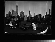 [Display: Dolls, Toy Cars, and Scale Model of Manhattan Skyline]
