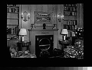 [Library Interior Showing Fireplace with Adjacent Bookshelfs and Armchairs]