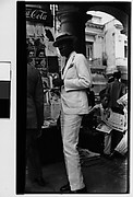 [Man in White Suit and Straw Hat in Front of Newspaper Kiosk, Havana]