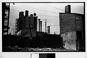 [Factory, Smokestacks, and Water Towers Behind Lot]