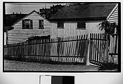 [Wooden Houses Behind Picket Fence]