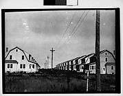 [Two Rows of Prefabricated Houses in Field]