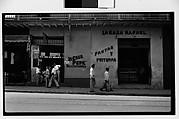 """[Street Scene in Front of Lottery Ticket Shop """"La Casa Pepe"""" and Fruit Market """"La Casa Rafael"""", Havana]"""