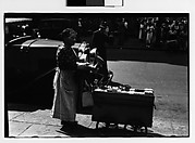 [Housegoods Vendor and Cart in Front of Parked Car, Fourteenth Street, New York City]