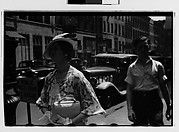 [Woman Passing Taxistand on Street, New York City]