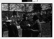 [Two Women in Conversation at Outdoor Country Auction with Graveyard in Distance]