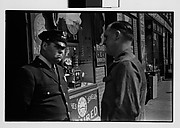[Man and Policeman in Conversation Outside Watch Repair Shop, New York City]