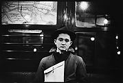 [Subway Passenger, New York City: Young Man in Hat Holding Parcel]