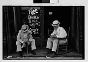 "[Two Elderly Men in Conversation on Porch in Front of Painted Sign for ""Free Dance"", Greensboro, Alabama?]"