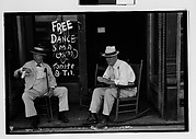 """[Two Elderly Men in Conversation on Porch in Front of Painted Sign for """"Free Dance"""", Greensboro, Alabama?]"""