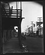 [Parked Cars and Warehouse Buildings on Cobblestone Street With Colonnade in Foreground, New Orleans, Louisiana?]