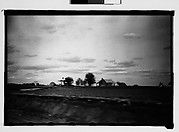 [Plantation and Surrounding Wooden Houses in Field, From Moving Automobile, Macon, Georgia]