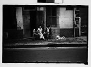 [People Seated on Sidewalk in French Quarter, New Orleans, Louisiana]