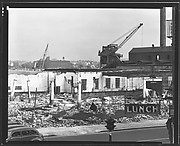 "[Demolition Site with Cranes, Cars on Street, and ""Lunch"" Sign in Foreground New York City]"