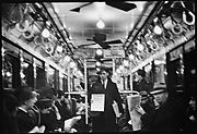 [View Down Subway Car with Newspaper Vendor in Aisle, New York City]