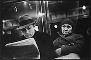 [Subway Passengers, New York City: Man Reading Newspaper, Elderly Woman]