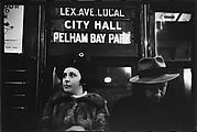 "[Subway Passengers, New York City: Woman, Man Beneath ""Lex Ave Local"" Sign]"