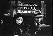 "[Subway Passengers, New York City: Woman in Fur Collar, Man Reading Newspaper Beneath ""City Hall"" Sign]"