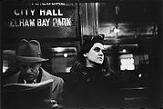 "[Subway Passengers, New York City: Man Reading Newspaper, Woman Beneath ""City Hall"" Sign]"