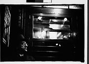 [Subway Passenger, New York City: Man Wearing Eyeglasses and Hat in Car Corner]