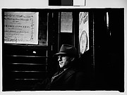 [Subway Passenger, New York City: Man Wearing Hat and Overcoat in Car Corner]