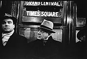 [Subway Passengers, New York City: Two Men Beneath Times Square Shuttle Sign]