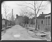 [View Down Street of Workers' Houses Leading to Factory Building]