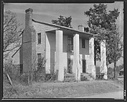 [House with Squared Columns and Rocking Chair on Porch]
