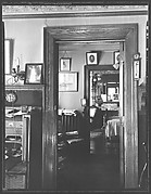 [Interior Showing Family Photographs Around Doorways and on Fireplace Mantle]