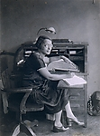 [Woman Seated at Desk]