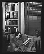 [Unidentified Woman Reading in Armchair in Library]