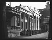 [Oblique View of Two Greek Revival Buildings Behind Cast-Iron Fence]