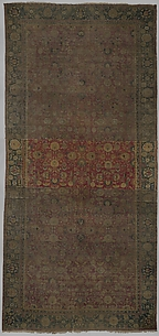 Indo-Persian carpet with repeat pattern of vine scrolls and palmettes.