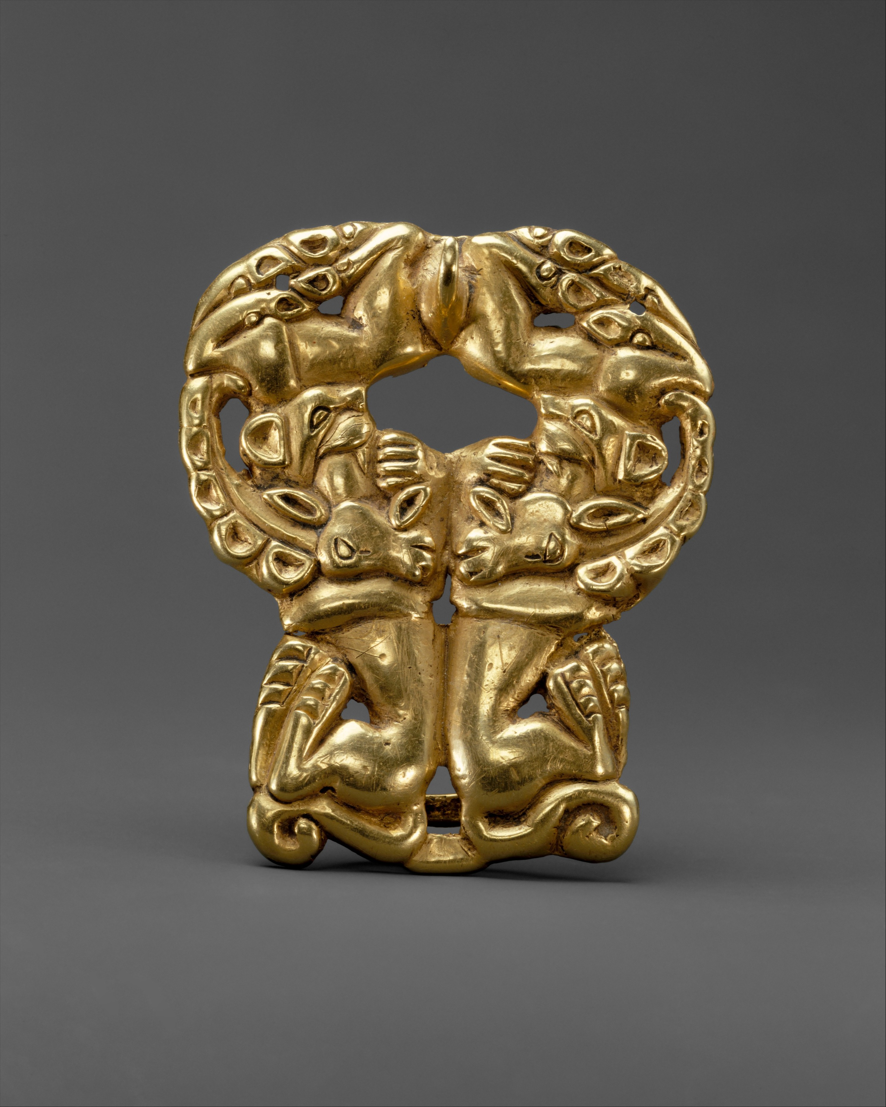 Belt buckle with paired felines attacking ibexes.