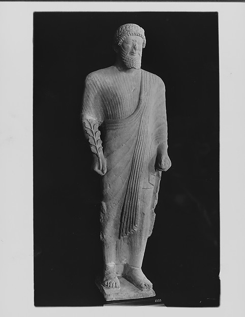 Limestone votary of a bearded male in Greek dress with a wreath, Limestone, Cypriot